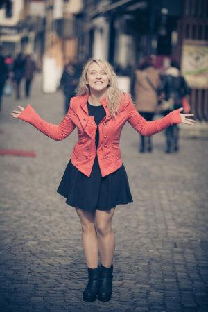 Kobieta w czerwonej kurtce rozkłada ręce i się uśmiecha