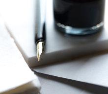 Wieczne pióro leży na notatniku obok kałamaża