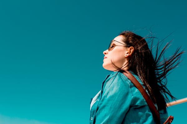 Kobieta w okularach przeciwsłonecznych patrzy w niebo