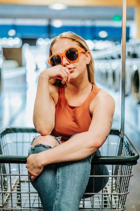 młoda dziewczyna siedzi w koszyku na zakupy